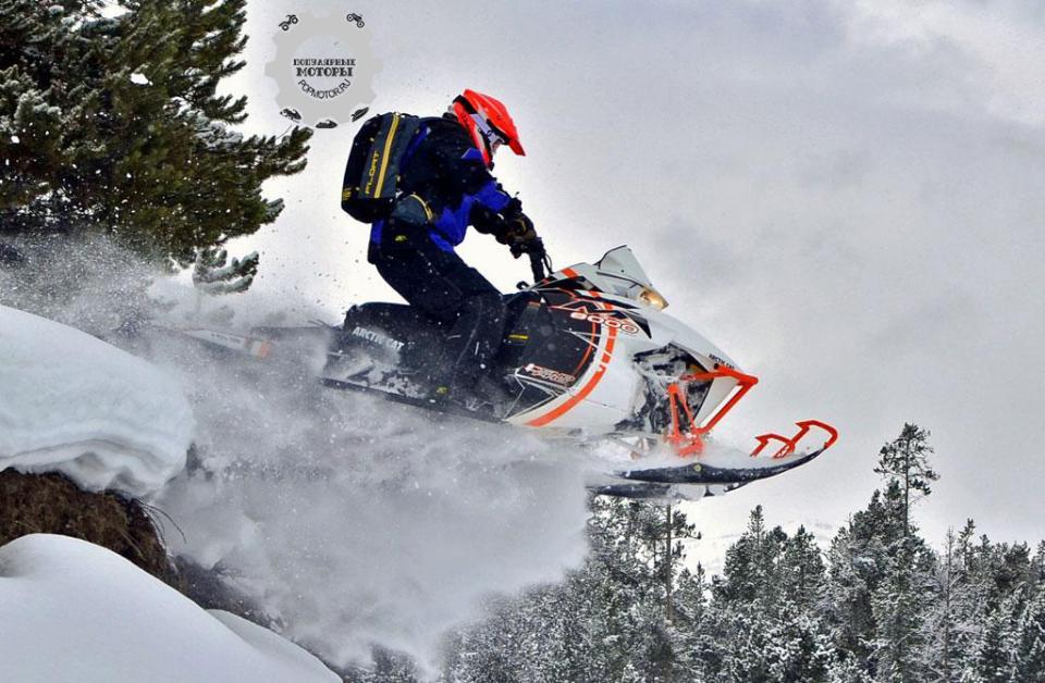 Съезжая с холма на мягкий снег, водитель-испытатель выжимает газ на новом M8000, и гусеница PowerClaw запускает снегоход в воздух.