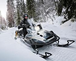 Мужчина едет по лесу на снегоходе Yamaha Viking 540