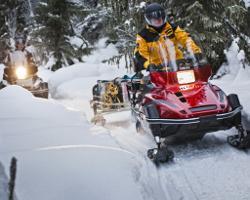 Люди едут по лесу на снегоходе Yamaha Viking