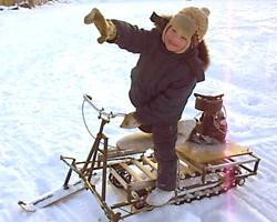 Ребенок на детском самодельном снегоходе